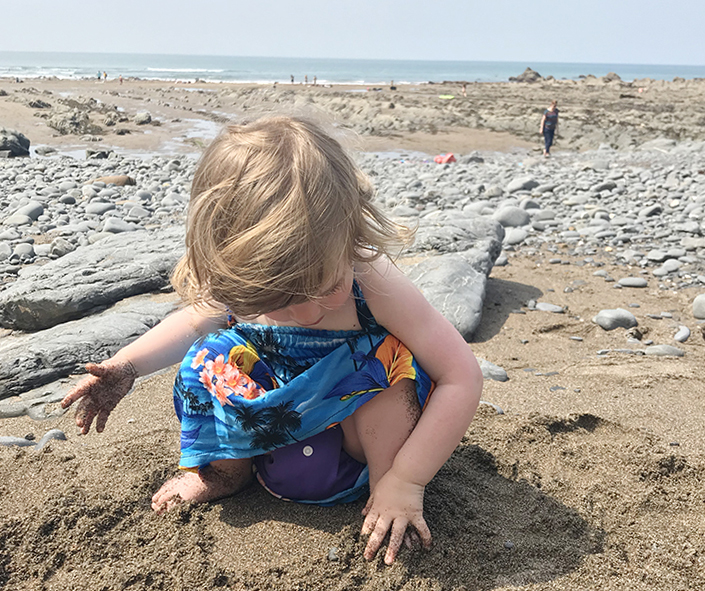 Sophie playing in the sand at beautiful Welcombe beach in Devon